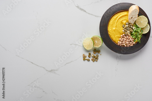 top view of autumnal mashed pumpkin soup in bowl near pumpkin seeds and lime on marble surface