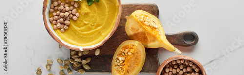 top view of autumnal mashed pumpkin soup in bowl on wooden cutting board near pumpkin, seeds and chickpea on marble surface