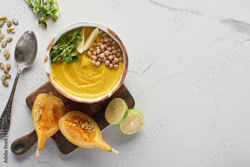 top view of autumnal mashed pumpkin soup in bowl on wooden cutting board near pumpkin, seeds, lime and spoon on marble surface