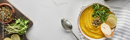 panoramic shot of tasty mashed pumpkin soup on wooden cutting board with ingredients on marble surface