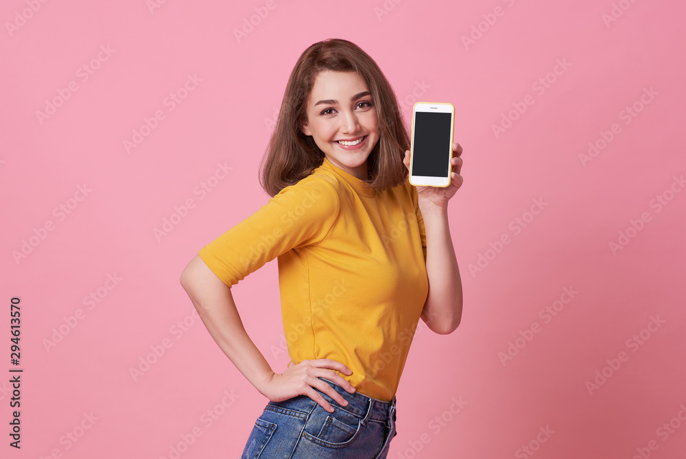 Fototapeta Portrait of happy young woman showing at blank screen mobile phone isolated over pink background.