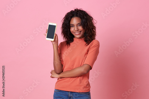 Pinturas sobre lienzo  Portrait of happy young african woman showing at blank screen mobile phone isolated over pink background