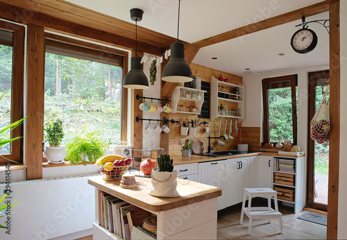 Obraz interior of modern kitchen in vintage style with white wooden furniture and rustic detail. Bright indoors with window and wood. - fototapety do salonu