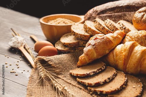 Fototapeta Different kinds of bread with nutrition whole grains on wooden background. Food and bakery in kitchen concept. Delicious breakfast gouemet and meal. Carbohydrate organic food cuisine homemade obraz