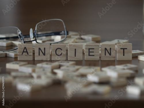 Fototapeta The concept of Ancient represented by wooden letter tiles