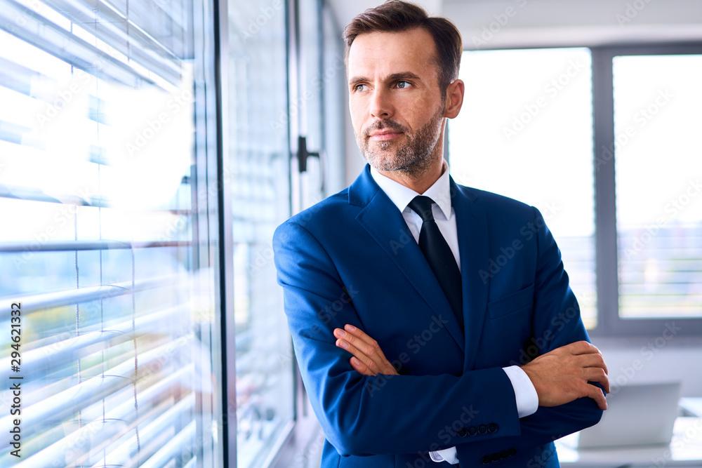 Fototapeta Portrait of adult businessman looking outside the window in office