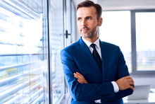 Portrait Of Adult Businessman Looking Outside The Window In Office