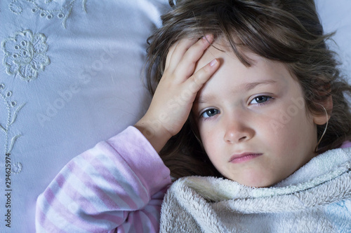 Exhausted child lying in bed, feeling sick Canvas Print