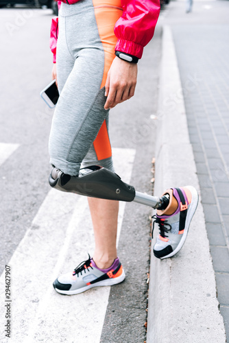 Photo partial view of disabled sportswoman with prosthesis holding smartphone on stree