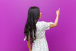 canvas print picture - young pretty latin woman standing and pointing to object on copy space, rear view against purple wall