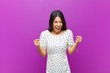 canvas print picture - young pretty latin woman feeling shocked, excited and happy, laughing and celebrating success, saying wow! against purple wall