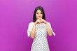 canvas print picture - young pretty latin woman looking serious and displeased with both fingers crossed up front in rejection, asking for silence against purple wall