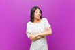 canvas print picture - young pretty latin woman shrugging, feeling confused and uncertain, doubting with arms crossed and puzzled look against purple wall