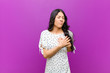 canvas print picture - young pretty latin woman looking sad, hurt and heartbroken, holding both hands close to heart, crying and feeling depressed against purple wall