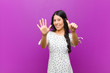 canvas print picture - young pretty latin woman smiling and looking friendly, showing number six or sixth with hand forward, counting down against purple wall