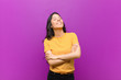 canvas print picture - young pretty latin woman laughing happily with arms crossed, with a relaxed, positive and satisfied pose against purple wall