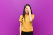 canvas print picture - young pretty latin woman looking sleepy, bored and yawning, with a headache and one hand covering half the face against purple wall