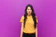 canvas print picture - young pretty latin woman looking shocked, angry, annoyed or disappointed, open mouthed and furious against purple wall