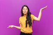 canvas print picture - young pretty latin woman shrugging with a dumb, crazy, confused, puzzled expression, feeling annoyed and clueless against purple wall