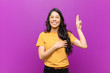 canvas print picture - young pretty latin woman looking happy, confident and trustworthy, smiling and showing victory sign, with a positive attitude against purple wall