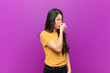 canvas print picture - young pretty latin woman feeling disgusted, holding nose to avoid smelling a foul and unpleasant stench against purple wall