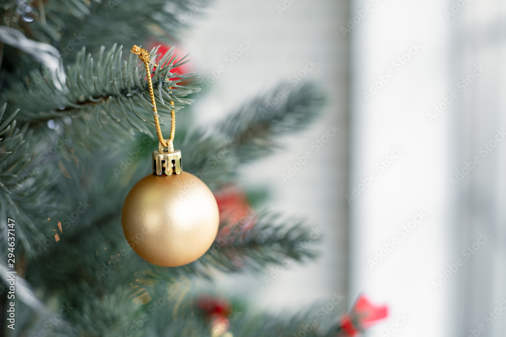 Fototapety, obrazy: Gold ball hanging from a decorated Christmas tree.