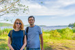 Tourists adult man and teenage girl posing against beautiful landscape in summer sunny day. Portraits of father and daughter on Ladoga lake shore. Travelling and discovering places. Karelia, Russia