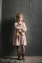 Upset Kid Looking At Camera While Standing With Soft Toy Near Wall, Post Apocalyptic Concept