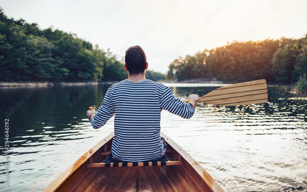 Fototapety, obrazy: Man in sailor shirt paddling canoe on the sunset lake