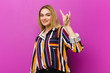 Leinwanddruck Bild - young blonde woman feeling happy, fun, confident, positive and rebellious, making rock or heavy metal sign with hand against purple wall
