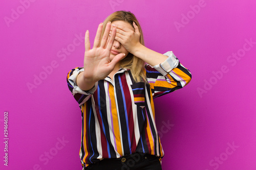 Fotografija  young blonde woman covering face with hand and putting other hand up front to st
