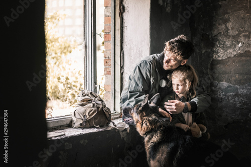 fototapeta na lodówkę man hugging kid near german shepherd dog in abandoned building, post apocalyptic concept