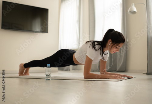 Young female planking with earphones and smartphone - 294648103
