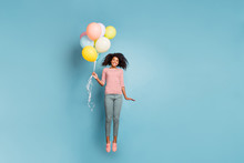 Photo Of Curly Wavy Cheerful Trendy Nice Young Girl Wearing Pants Trousers Striped T-shirt Flying Up Holding Baloons Isolated Over Blue Pastel Color Background