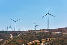 Shot Of A Windmills Against A Blue Sky And Green Hills, Wind Power Technology. View On Turbine. Cyprus.