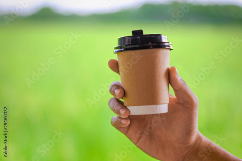 Foto auf Gartenposter Lime grun A hand holding a paper cup of coffee among nice scenery