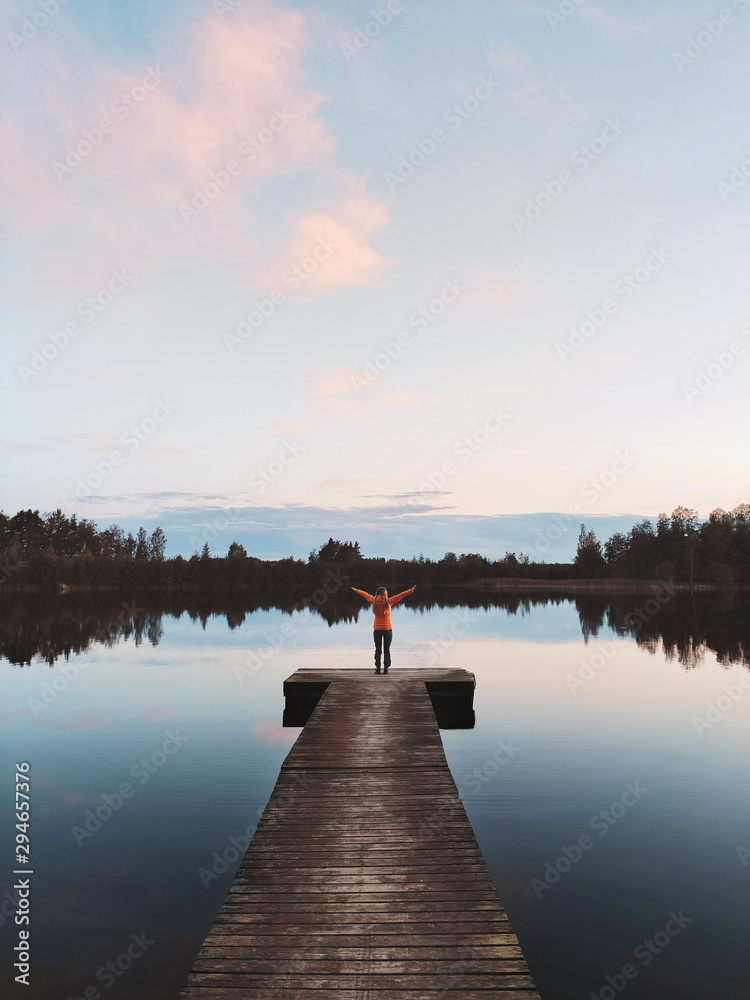 Fototapety, obrazy: Woman traveler standing alone on pier enjoying sunset lake and forest view traveling outdoor vacations in Finland