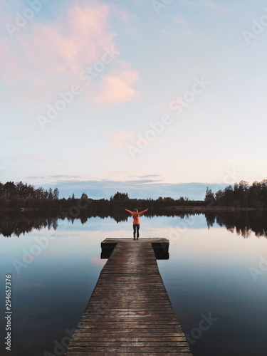 Woman traveler standing alone on pier enjoying sunset lake and forest view trave Fototapet