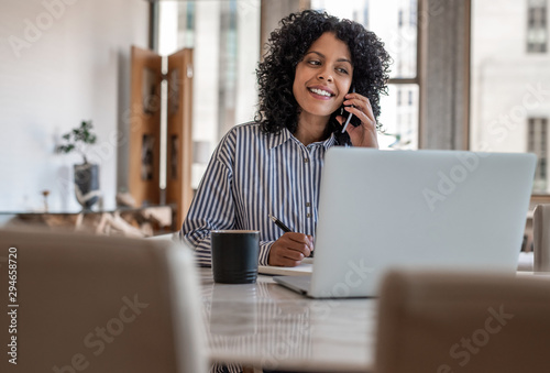 Smiling female entrepreneur sitting at home talking on her cellphone Canvas Print