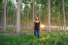 Latin Brunette Woman Walks Among The Trees Of A Forest At Sunset. The Sun's Rays Enter Through The Vegetation. She Wears A Brown Sweater, A Black T-shirt And A Jeans.
