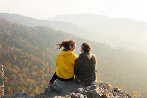 Couple in love sitting at the top of the mountain and watching autumn landscape Canvas Print