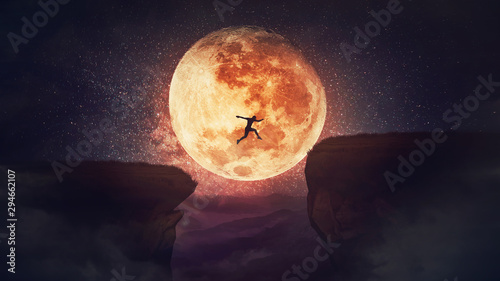 Cuadros en Lienzo  Surreal scene, self overcome concept, as determined man jump over a chasm obstacle