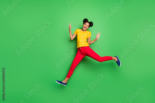 Full length photo of pretty dark skin lady jumping high sports competition jogging participant wear casual yellow t-shirt red pants isolated green background