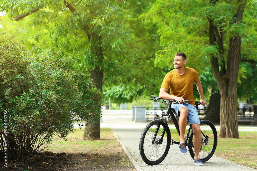 Fototapety, obrazy: Handsome man with modern bicycle in park