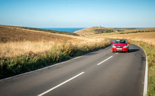 Road Trip; South Downs, England. A Car Travelling A Winding Road In East Sussex With Belle Tout Lighthouse And The English Channel In The Distance.