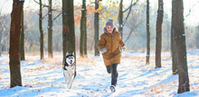 Running Boy With Husky On A Distillation In A Winter Park