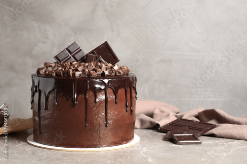 Fototapeta Freshly made delicious chocolate cake on marble table against grey background. Space for text obraz