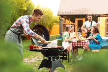 Group Of Friends At Barbecue Party Outdoors. Young Man Near Grill