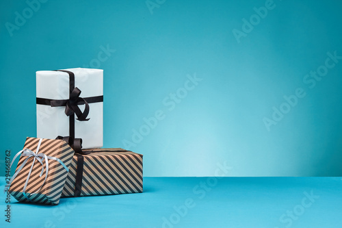 Fotomural  Different sizes, colorful, striped and plain paper gift boxes tied with ribbons and bows on a blue surface and background