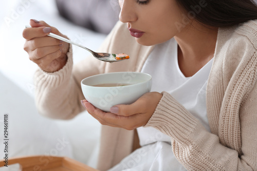Fotografie, Tablou Sick young woman eating soup to cure flu at home